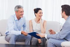 Salesman and clients talking and laughing together on sofa Stock Photos