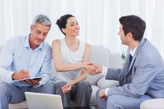 Salesman closing a deal with a couple - stock photo