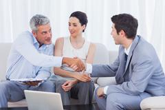 Salesman closing a deal with a smiling couple - stock photo