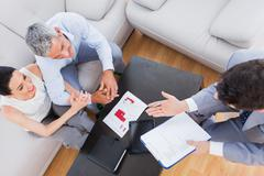 Salesman making his pitch to couple - stock photo