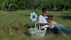 Mommy And Son Reading Book In Park - stock footage