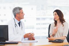 Patient talking with her doctor about illness - stock photo