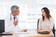 Serious patient talking with her doctor about illness - stock photo