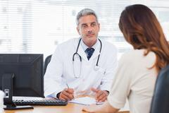 Doctor listening to his patient talking about her illness - stock photo
