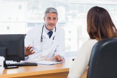 Doctor explaining an illness to his patient - stock photo