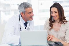 Docter showing something on laptop to his patient - stock photo