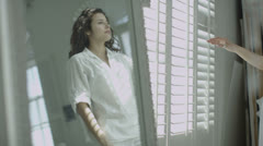 Beautiful woman in elegant apartment and sunlight streaming through the shutters - stock footage
