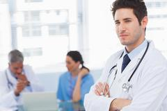 Serious doctor looking at camera with colleagues behind Stock Photos