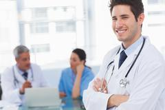 Stock Photo of Happy doctor looking at camera with colleagues behind