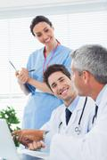 Happy nurse listening to doctors talking about something on their laptop - stock photo