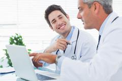 Doctors talking together about something on their laptop Stock Photos