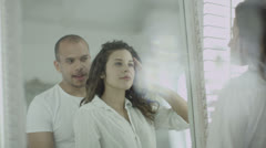 Beautiful young couple embrace and stare at their reflections in the mirror  Stock Footage