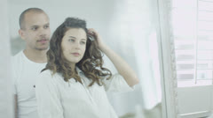 Beautiful young couple embrace and stare at their reflections in the mirror  - stock footage