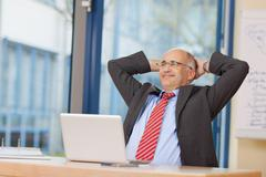 businessman with hands behind head sitting at desk - stock photo