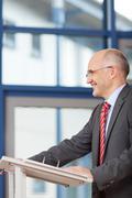 Stock Photo of mature businessman standing at podium