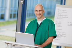 confident mature surgeon standing at podium - stock photo