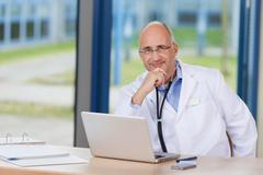 male doctor with hand on chin and laptop on desk - stock photo