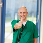 Stock Photo of male surgeon showing thumbs up sign