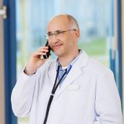 doctor conversing on cordless phone in clinic - stock photo