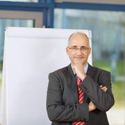 Mature businessman with arm on chin by flipchart Stock Photos