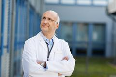 Doctor with arms crossed looking away Stock Photos