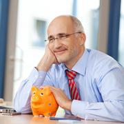 Businessman with piggybank looking away at desk Stock Photos