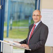 Stock Photo of confident mature businessman standing at podium