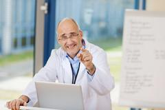 Stock Photo of mature male doctor pointing in clinic