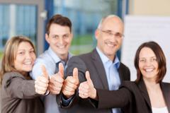 People showing thumbs up sign in office Stock Photos