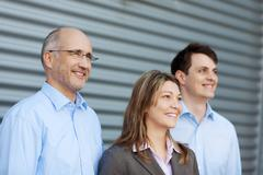 Stock Photo of businesspeople looking away against shutter