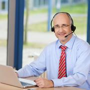 Male customer service executive wearing headset while using lapt Stock Photos