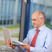 Mature businessman holding laptop Stock Photos