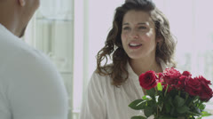 Man surprises his wife or girlfriend with bouquet of red roses - stock footage