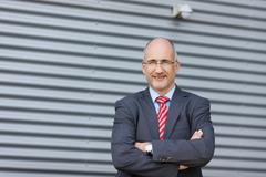 businessman with arms crossed standing against wall - stock photo