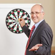 businessman gesturing while holding dart attached to target on f - stock photo