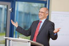 businessman with arms raised standing at podium - stock photo