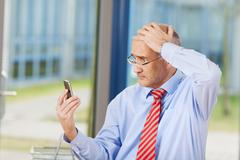 Businessman reading message on mobile phone Stock Photos