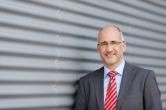 businessman standing against building - stock photo