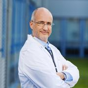 confident male doctor with arms crossed - stock photo