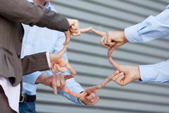 businessteam joining fingers against shutter - stock photo
