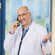 male doctor gesturing while using cordless phone - stock photo