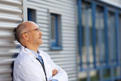 doctor leaning on wall while looking away - stock photo