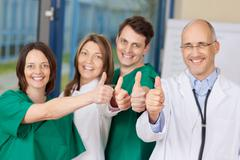 Team of doctors gesturing thumbs up sign Stock Photos