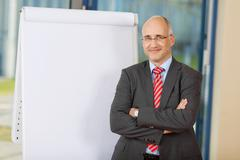 mature businessman with arms crossed standing by flipchart - stock photo