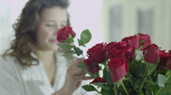 Beautiful young woman arranging a vase of red roses and relaxing at home - stock footage