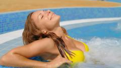 Young, attractive, nice, beautiful woman lies in the jacuzzi Stock Footage