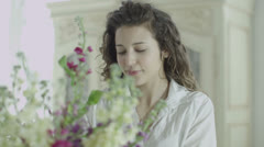 Beautiful woman arranging vase of flowers and relaxing with her partner at home Stock Footage
