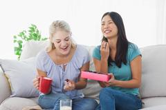 Friends sharing a box of chocolates and laughing Stock Photos