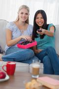 Friends sharing a box of chocolates and watching tv - stock photo