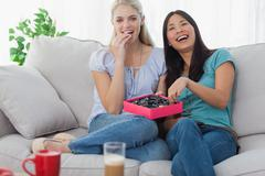 Friends laughing and sharing box of chocolates Stock Photos